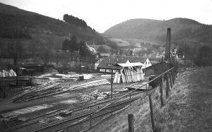 """Das Sägewerk Dartenne auf Gangfort am 11. Februar 1951, gesehen vom unteren """"Hähnchen. Die """"Gebrüder Dartenne OHG, Säge- und Hobelwerke"""" unter Leitung von Karl Dartenne beschäftigte je nach Jahreszeit zwischen 20 und 40 Mitarbeiter. Das Werk hatte einen eigenen Gleisanschluss, dessen Prellbock kurz vor dem Bahnübergang der B 258 stand. Anfangs wurden die Holzwaggons mittels Muskelkraft und Knippstangen"""" bewegt. Später hatte das Werk eine Draisine, die vom Motor eines Opel p 4 angetrieben wurde."""